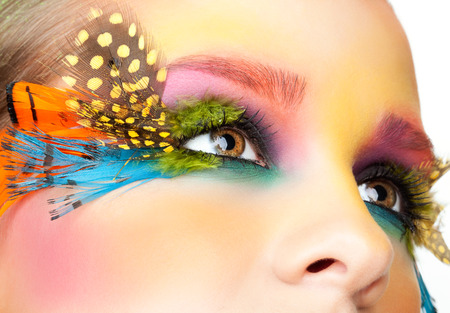 Young pretty woman face with false feather eyelashes fashion makeup