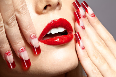open lips: Fingers with red french acrylic nails manicure and paiting