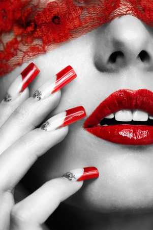 finger tip: Woman part of face with eyes closed by red ribbon and with red french acrylic nails manicure Stock Photo