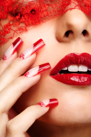 Woman part of face with eyes closed by red ribbon and with red french acrylic nails manicure photo