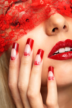 Woman part of face with eyes closed by red ribbon and with red french acrylic nails manicure Standard-Bild