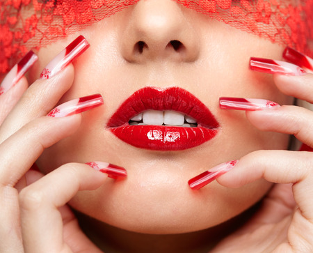 naildesign: Woman part of face with eyes closed by red ribbon and with red french acrylic nails manicure Stock Photo