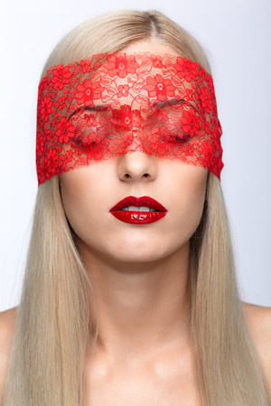 closed ribbon: Blonde woman face with eyes closed by red ribbon  Stock Photo