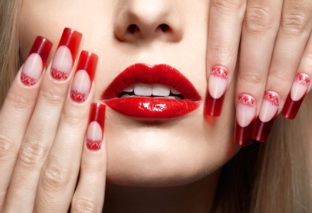 Fingers with red french acrylic nails manicure and paiting photo