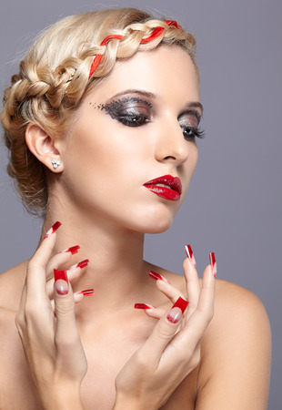 french model: Young blonde woman with braid hairdo and red nails on gray background
