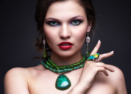 Portrait of beautiful young brunette woman in malachite necklace, pendent, ring and earrings on dark gray background photo