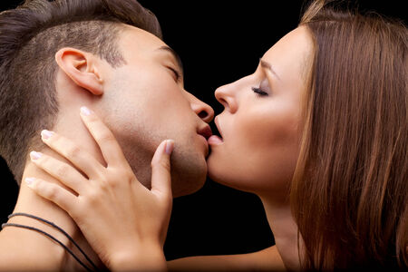 Young couple of lovers kissing on black background photo