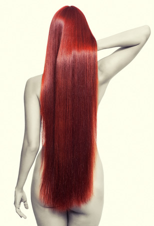 Portrait of beautiful young nude woman with long red hair. View from back side photo