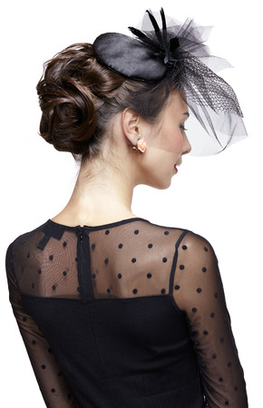 frenchwoman: Young woman in vintage dress and small female hat with veil. Shot from behind