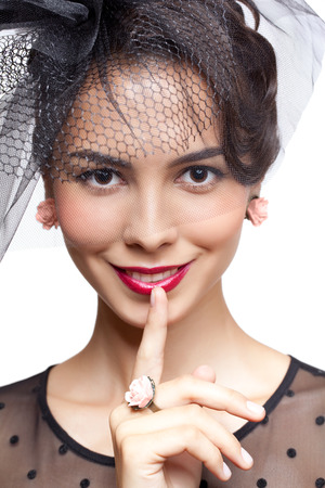 Young woman in vintage dress and small female hat with veil isolated on white with finger on lips photo