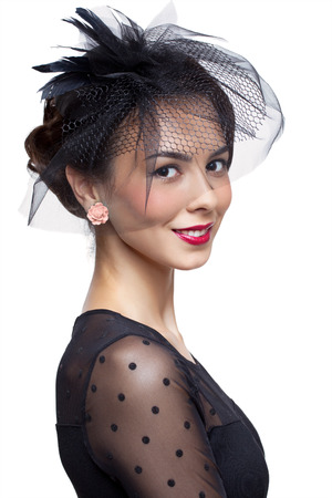 spotty: Young woman in vintage dress and small female hat with veil isolated on white Stock Photo