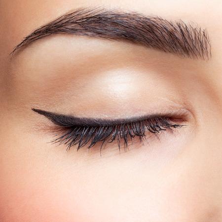若い美しい女性の閉鎖のクローズ アップの肖像画は、黒の矢印で目もとを作る