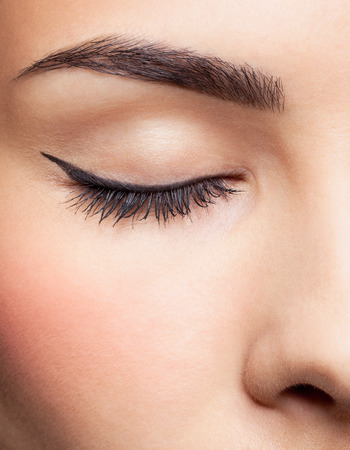 close-up portrait of young beautiful womans closed eye zone make up with black arrow
