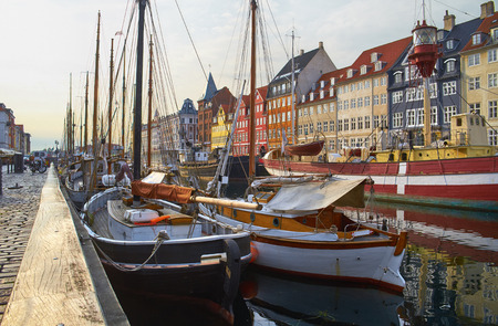 entertainment district: The boats and ships in the calm hurbour of Nyhavn, Copenhagen, Denmark. Nyhavn  (New Harbour) is waterfront, canal and entertainment district in Copenhagen.