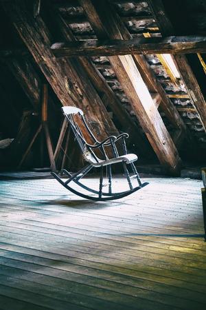 デンマーク、コペンハーゲン ラウンド タワーに捨てられた古い屋根裏部屋の床にビンテージのロッキングチェア。