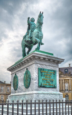frederik: COPENHAGEN, DENMARK - AUGUST 22, 2014:  Equestrian bronze statue of King Frederik V in Amalienborg Square in Copenhagen, Denmark. The statue was created by the French sculptor Jacques Saly in 1768. The statue represents Frederick V of Denmark in classic a Editorial