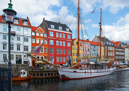 COPENHAGEN, DENMARK - AUGUST 22, 2014: The Nyhavn canal.  Nyhavn  (New Harbour) is waterfront, canal and entertainment district in Copenhagen.  It is lined by brightly coloured 17th and early 18th century townhouses and bars, cafes and restaurants. Servin