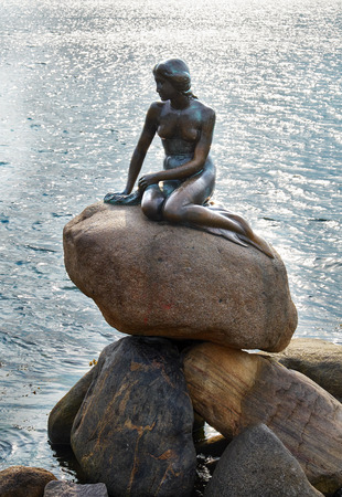 historical sites: COPENHAGEN, DENMARK - AUGUST 22, 2014: Little Mermaid statue. The monument of Little Mermaid is one of the biggest tourist attractions in Copenhagen and Denmark