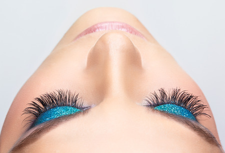 eye lashes: Woman face with blue shining eye make-up