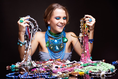Laughing young beautiful woman over heap of bijouterie on the table with beads in hands photo