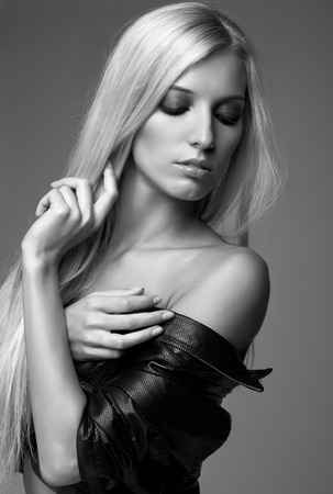 grayscale: Monochrome portrait of blonde young woman in black jacket on gray background