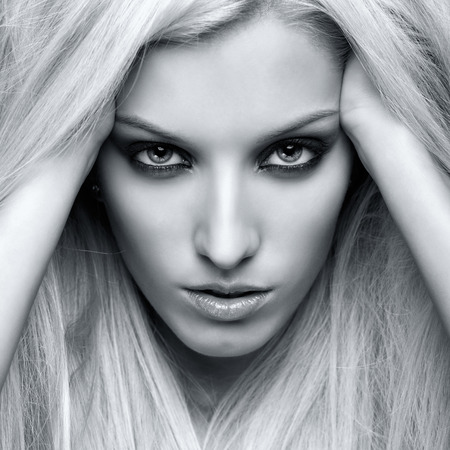 girl with gray eyes: Monochrome portrait of blonde young woman on gray background