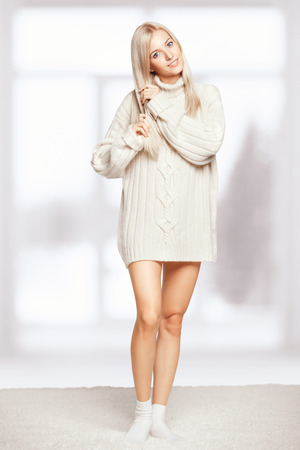 long socks: Blonde young woman dressed in long white cashmere sweater on white whole-floor carpet and window background Stock Photo