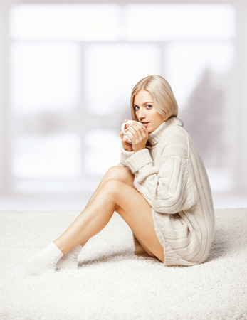 Blonde young woman dressed in large white cashmere sweater and seating on on white whole-floor carpet on window  background drinking a cap of tea photo