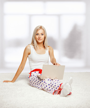 Young blonde woman in pyjamas on white whole-floor carpet browsing laptop  near window