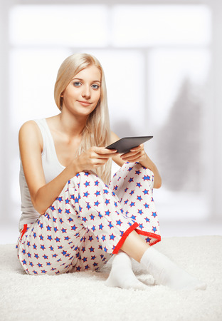 Young blonde woman in pyjamas on white whole-floor carpet reading e-book  near window