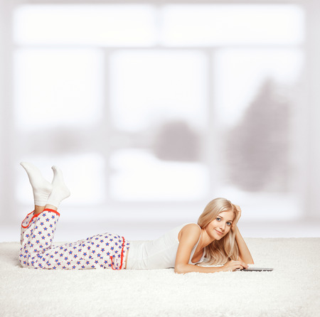 white socks: Young blonde woman in pyjamas on white whole-floor carpet reading e-book Stock Photo