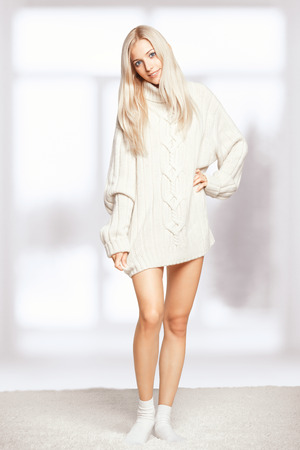 long socks: Blonde young woman dressed in long white cashmere sweater on white whole-floor carpet