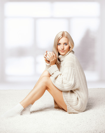 Blonde young woman dressed in large white cashmere sweater and seating on on white whole-floor carpet photo