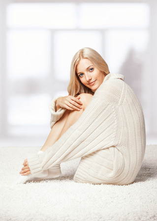 Blonde young woman dressed in long white cashmere sweater sitting on white whole-floor carpet photo