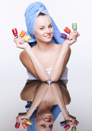 Young pretty spa woman in blue bath towel on head with nail varnish over mirror table on white background photo