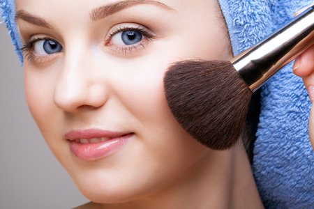 brush in: woman in blue bath towel on head with makeup brush Stock Photo
