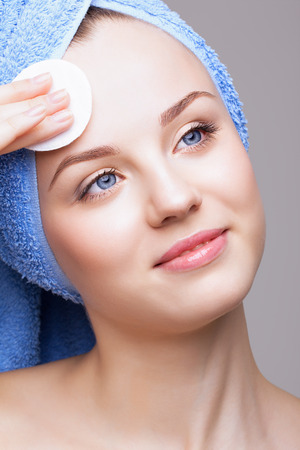 cotton pad: woman in blue bath towel on head with makeup cotton pad