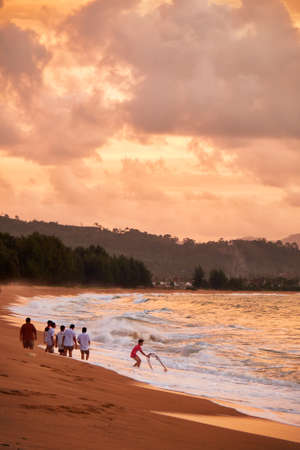 croud: People fishing at the time of sunset on Mai Khao beach in Phuket, Thailand