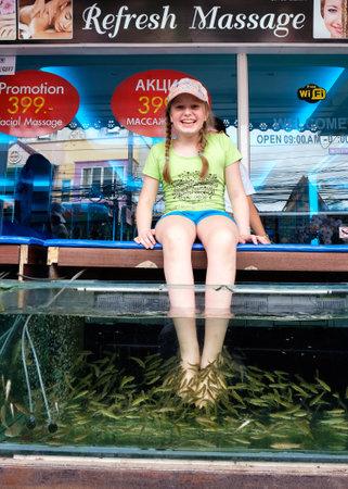 fish spa: PHUKET, THAILAND -  NOVEMBER 04, 2014: Young happy girl on fish spa procedure in Karon spa salone on Phuket, Thailand.