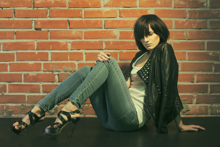 girl sit: Androgyny female model in Heroin chic style near brick wall. Old style tinted image