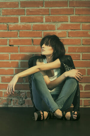 emaciated: Androgyny female model in Heroin chic style near brick wall. Old style tinted image
