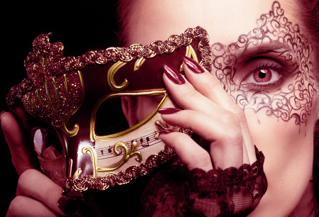 Close-up portrait of beautiful brunette woman with facial body art hiding half of her face with carnival venetian mask in marsala colors photo