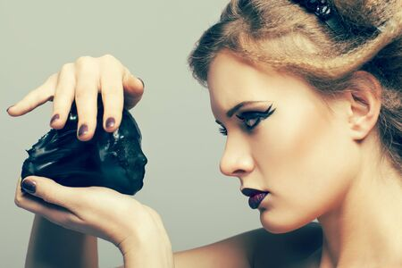 alien women: Woman in dress and diadem made of melted vinyl disk with alien face in hands Stock Photo