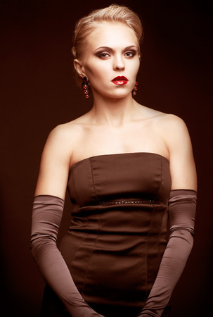 long gloves: Young blonde woman in black dress and long gloves on dark background toned in marsala color Stock Photo