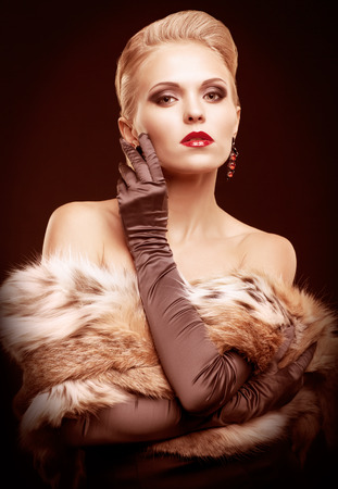 long gloves: Young blonde woman in black dress and lynx fur with and long gloves on dark background toned in marsala color Stock Photo
