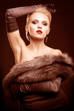 silver fox: Mujer rubia joven en vestido negro y piel de zorro plateado con y guantes largos en fondo oscuro en tonos color marsala