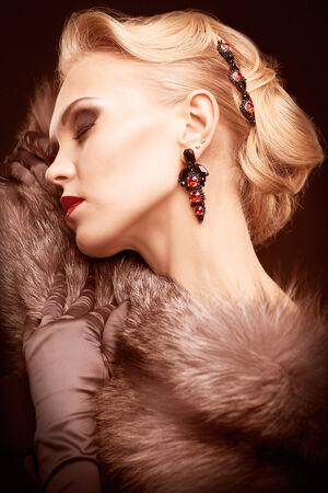 silver fox: Mujer rubia joven en vestido negro y piel de zorro plateado sobre fondo oscuro en tonos color marsala Foto de archivo