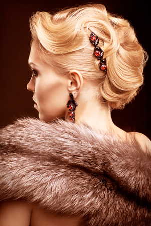 Young blonde woman in black dress and fur of silver fox on dark background toned in marsala color
