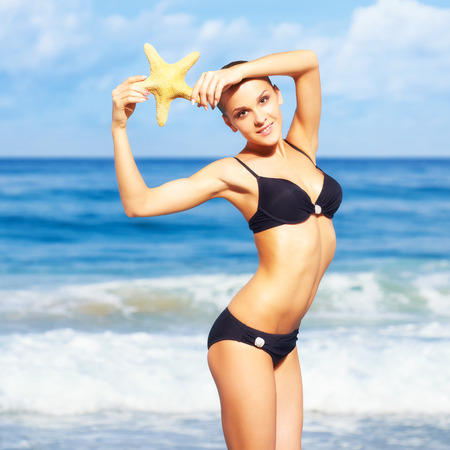 portrait of young beautiful woman in black bikini posing with finger-fish on sea background photo