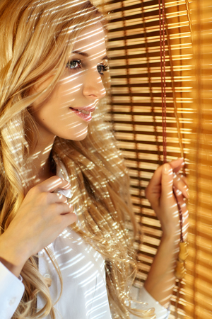 Young blonde beautiful happy woman looking looking out the window through the bamboo blinds with Sun hotspots on the face photo